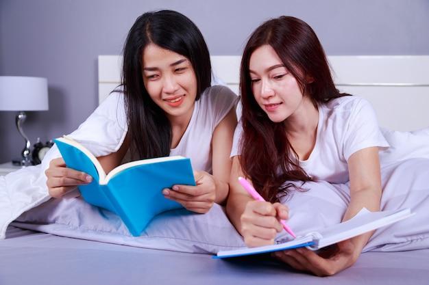 ベッドルームにベッドで本を書いて読んでいる2人の女性