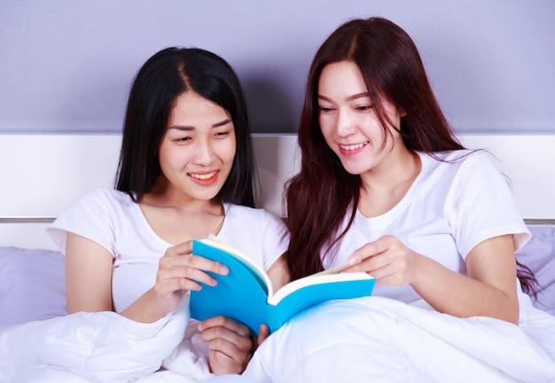 ベッドルームにベッドで本を読んでいる2人の女性