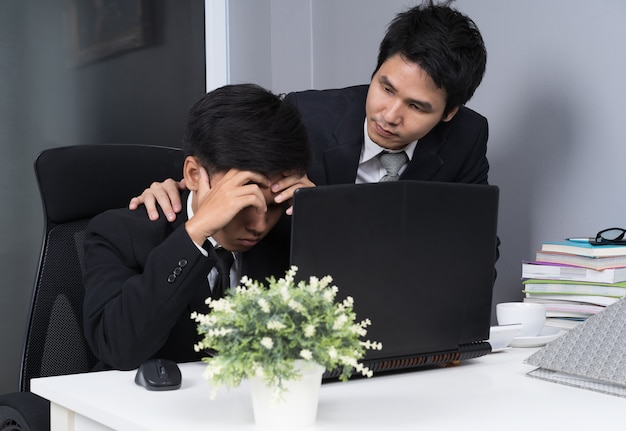 深刻な2つのビジネスマンは、作業用のプロジェクトにラップトップを使用して強調