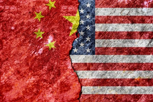 ひびの入ったコンクリートの壁の背景にアメリカと中国の旗。 2つの超大国の概念の対立。