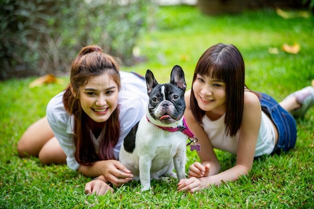 2人の女性が庭で小さな犬と遊ぶ