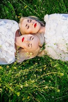 緑の芝生に横になっている2人の姉妹の双子