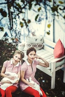 2人の美しい双子の姉妹がウサギと一緒に座る