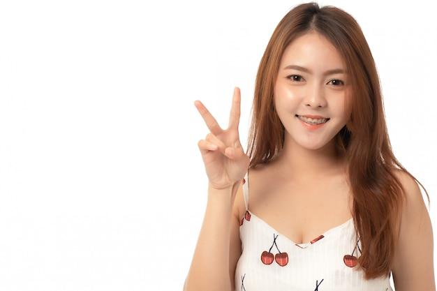 陽気なアジアの女性の笑顔と白で隔離される2本の指でピースサインを示す画像
