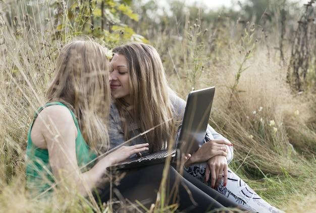 屋外で一緒に座っている2人の女性の友達