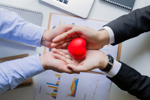赤いハートを保持している2つのビジネスマン。成功の心。成功の概念