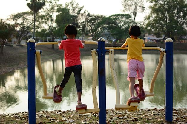 タイの公園で遊び場を遊んでいる2人の子供たち