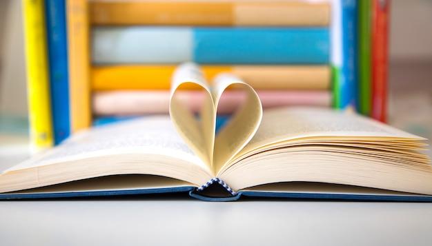 ハートのディテールの形に折り畳まれた2ページの本を開く