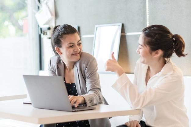 オフィスで議論する幸せな2つの美しい実業家オフィスワーカー