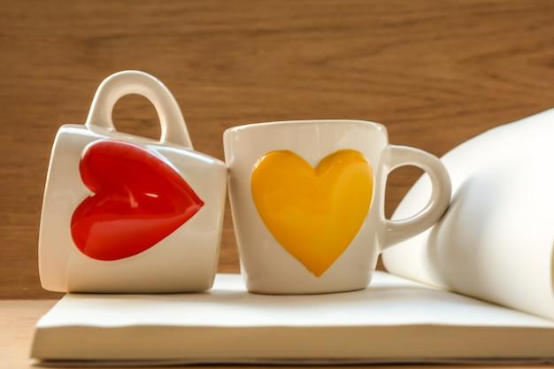 赤と黄色のハート型の本に2つのカップ