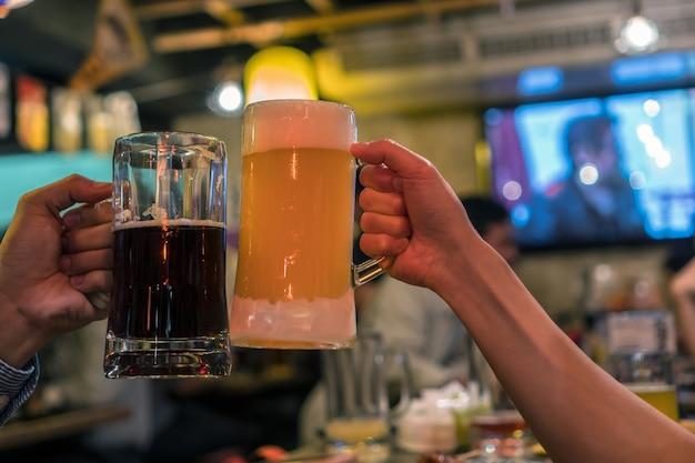 ビールの2つの眼鏡は、バーとレストランの友人の間で一緒に歓声をあげる