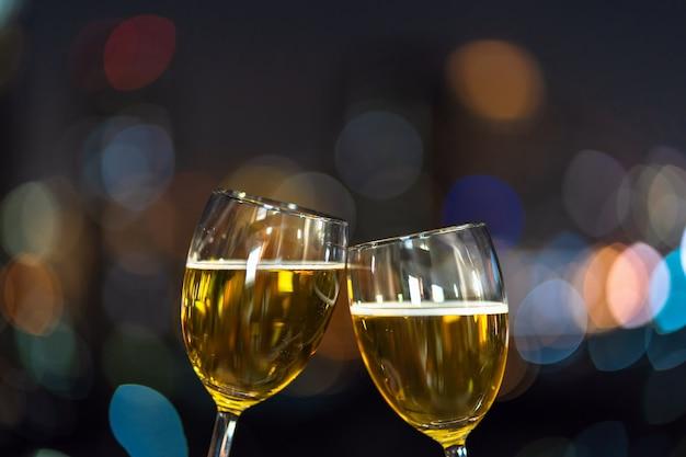 お祝いのために街並みがぼやけた写真の上に2つのビールマグカップやメガネをかぶせて