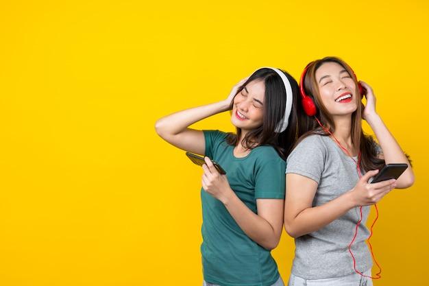 スマート携帯電話経由で音楽を聴くと孤立した黄色の壁に踊るワイヤレスヘッドフォンを着て2つの幸福アジア笑顔若い女性