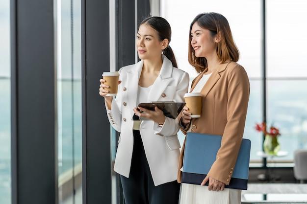近代的なオフィスやコワーキングスペースでのコーヒーブレーク中に話している2人のアジアのビジネスウーマン