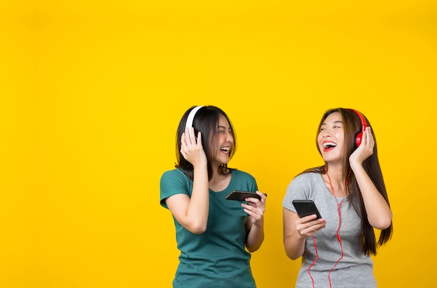 スマート携帯電話を介して音楽を聴くためのワイヤレスヘッドフォンを着て2つの幸せアジア笑顔若い女性