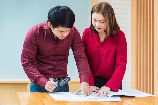 2つのエグゼクティブビジネスマンと女性は、彼らのアーキテクチャの青写真を見て
