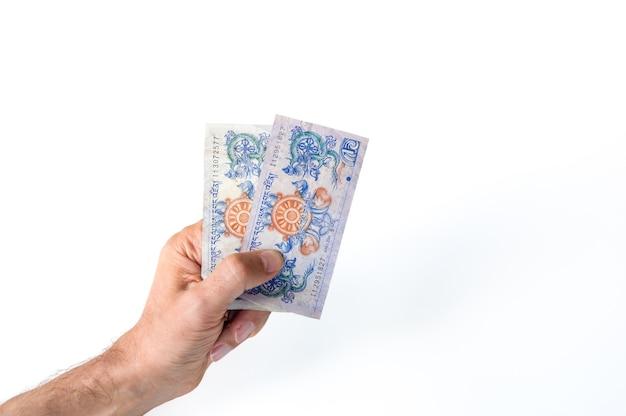 彼の手に2つのブータン・ヌルルタム紙幣を持っている男