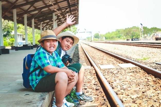 旅行を待っている電車に座っている2人のアジアの少年