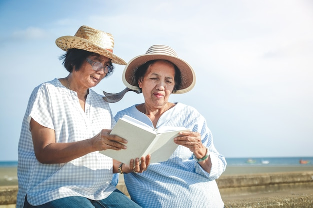 本を読んでビーチに座っている2人のアジアの高齢女性