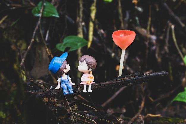 シャンパンマッシュルームの下に座ってキスしようとする2つの小さな人形。