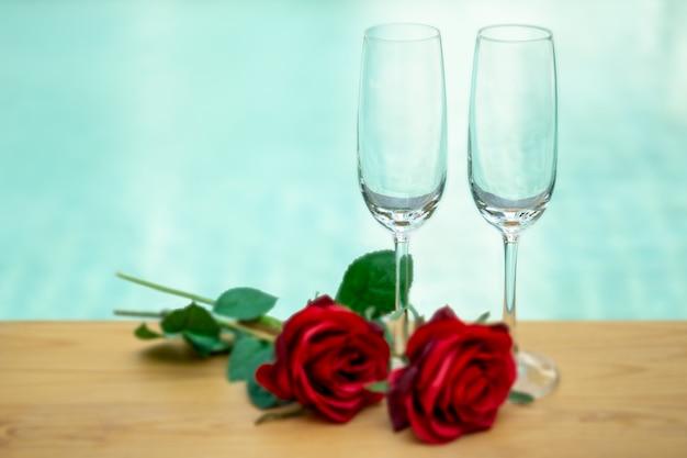 バラの花を持つ2つの空のシャンパングラス