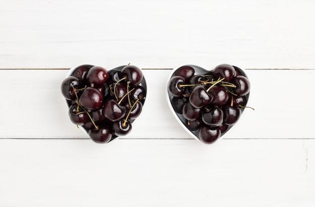 白い木の上の2つのハート型のボウルに新鮮な熟した赤と黒のチェリー。