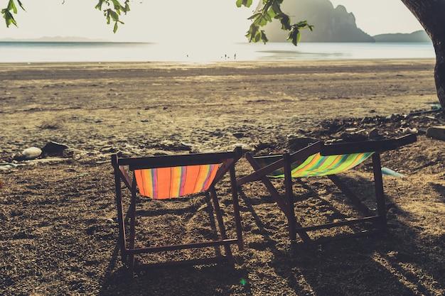空の2つのビーチチェアヴィンテージ色のトーン夏の休日の概念