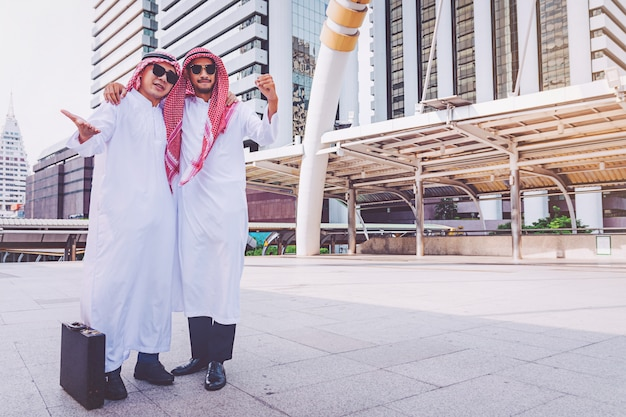 市内で両手を上げることによって立っている2人のアラブのビジネスマン