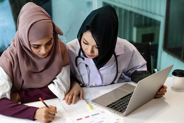 ラップトップを使用して2人の女性医師が患者についての相談、病院での勤務、忙しい時間