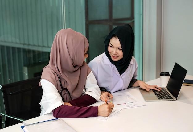 ラップトップを使用して2人の女性医師が患者の治療、忙しい時間、病院での勤務について相談する