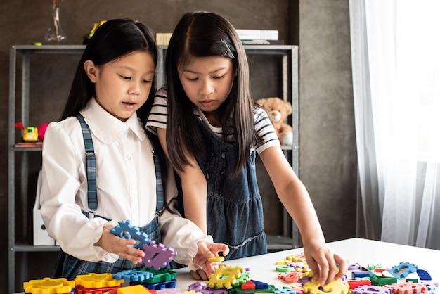 机の上のカラフルなレゴを演奏する2つの小さな女の子