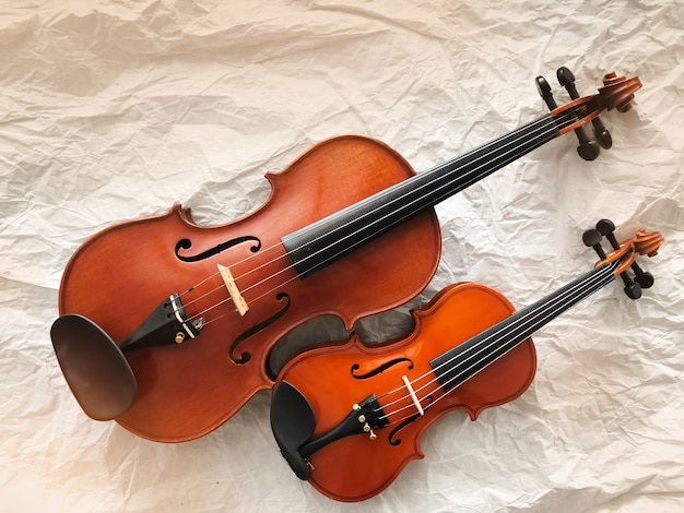背景の上に置かれた2つの異なるサイズのバイオリン、暖かいライトトーン
