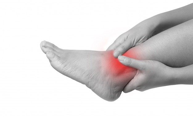 足を押しながら痛みを伴うマッサージの2つの手を使用して足首の痛みを持つ女性