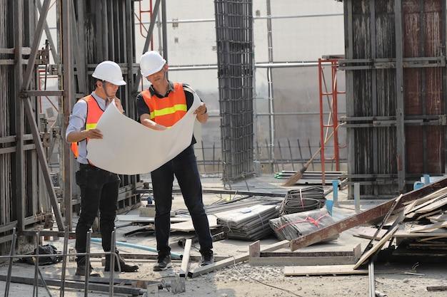 2人のエンジニアが建設現場で働いています。彼らは作業の進行状況をチェックしています。