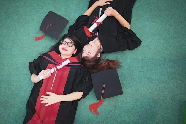 2人の美しいアジアの女性が卒業式の日に緑の芝生に寝転んでいます。