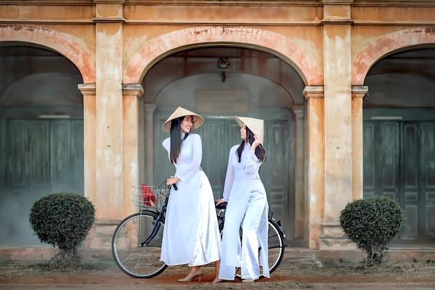 ベトナムの民族衣装を着た2人の美しい女性が自転車に乗って古代の建物を見ます。