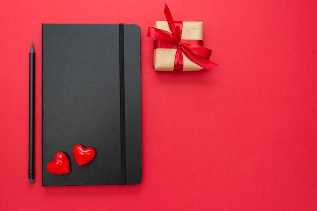 赤い背景の2つの心とギフトボックスに黒のノートブック。バレンタインデーのコンセプト。