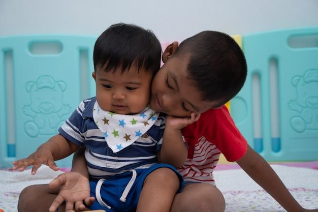 部屋で遊ぶかわいい2つの小さな男の子