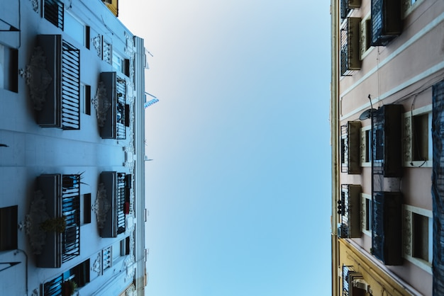 Предпосылка неба между 2 старыми зданиями.