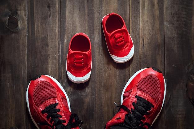 2つの赤いスポーツシューズまたはスニーカー母親または父親と子供の木製の背景