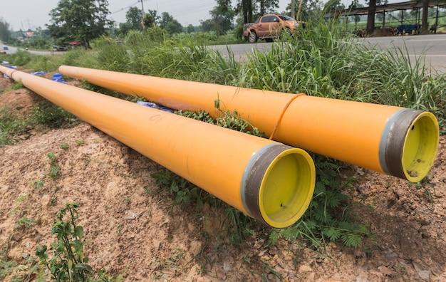2つの排水管黄色のプラスチックパイプ移送水システムは、現場に整列しています。