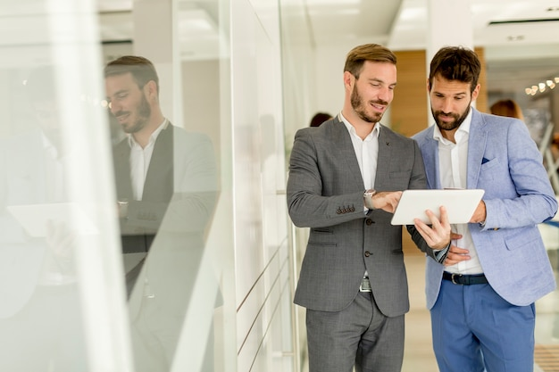 オフィスでデジタルタブレットを持つ2つの若いビジネスマン