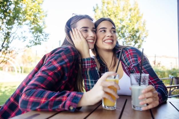 公園でジュースとレモネードを飲む2人の若い女性
