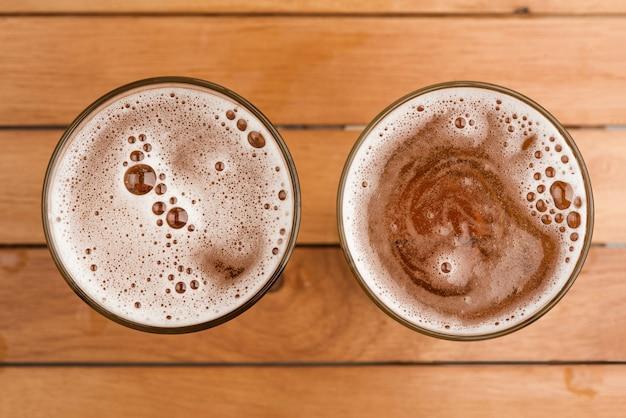 トップビューの木製の背景にガラスの上の泡とビールの2つのマグカップ