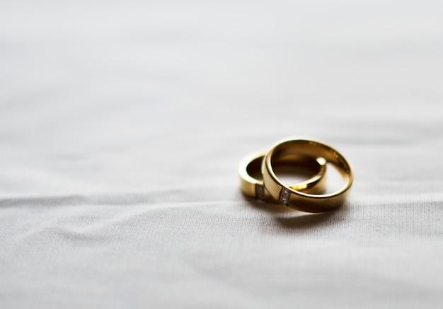 白い背景に2つの金の結婚指輪