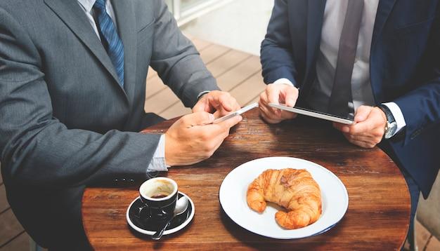 2人のビジネスマンのカフェ会議ワイヤレスタブレットのコンセプト