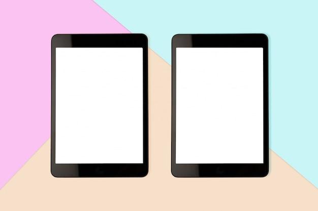 パステルカラーの背景、フラットレイアウト写真の空白の画面を持つ2つのデジタルタブレットをモックアップします。