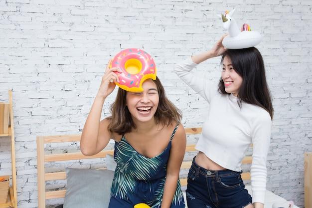 Счастливая азиатская девушка 2 играя с поплавком пончика