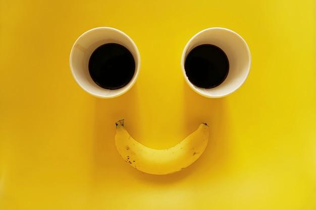 黄色の背景にバナナとコーヒーの2つの紙コップの笑顔