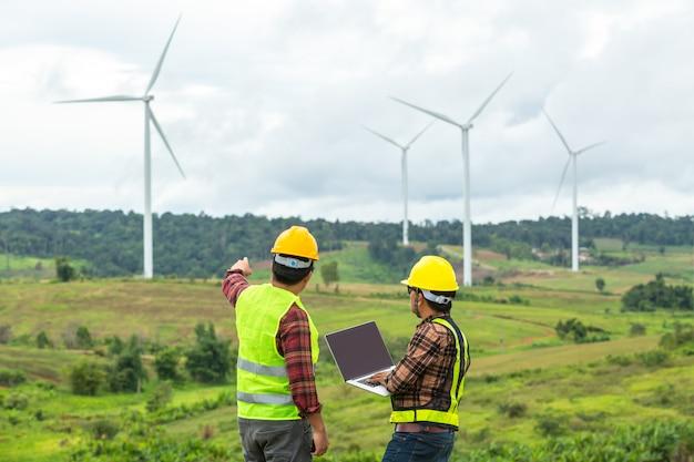 2台の風車エンジニアの検査と進捗状況は、建設現場で車を車両として使用して風力タービンをチェックします。